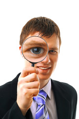 young man looks through a magnifying glass..