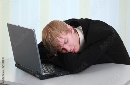 A stressed businessman with his forehead resting on the laptop