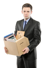 A fired man in a suit carrying a box of personal items
