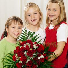 Kinder warten mit Blumenstrauß auf die Mutter