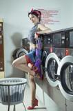 Frau steht imWaschsalon vor Waschmaschine