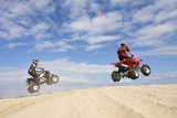 Two Quads jumping sand dunes