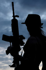 Silhouette of woman with assault rifle.