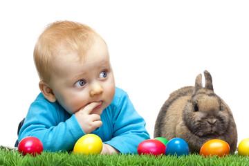 Baby sitzt in grüner Wiese mit Osterhasen und bunten Ostereiern