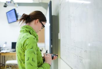 young female college student in front of a whiteboard using a ca