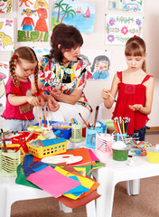 Children with teacher draw paints in playroom.