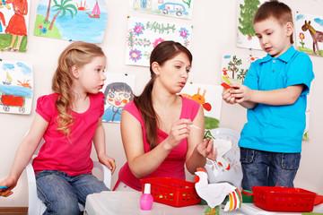 Children with teacher  glue picture in preschool. Child care.