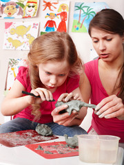 Child with teacher  mould from clay in play room. Child care.