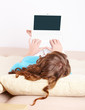 Young woman laying on sofa and using laptop