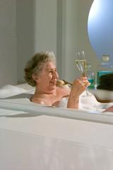 Oma in der Badewanne trinkt Champagner