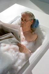 Baden, Opa in der Badewanne liest Zeitung
