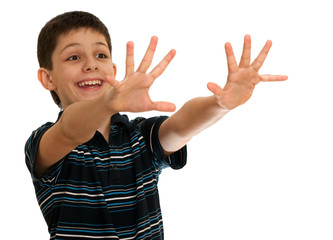 Spontaneous boy is stretching his hands towards an invisible aim