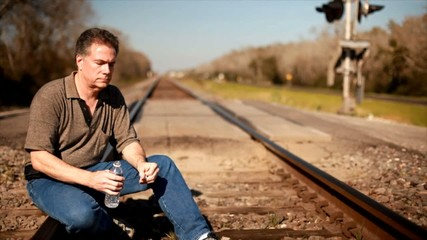 A man sitting on a railroad track drinking some water.