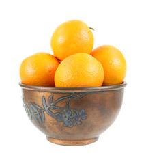Several fresh oranges in an old copper metal bowl