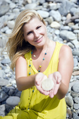 young beautiful woman in stone zen garden holding stones