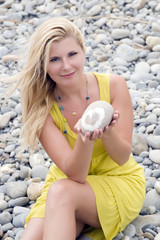 Conceptual photo of young beautiful woman holding pebble stone