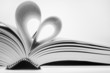 opened book with pages folded in heart shape