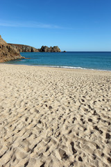 Porthcurno sandy beach and Logan rock in Cornwall UK.