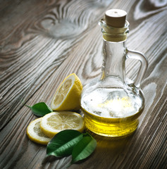 Olive oil and Lemon over wooden background
