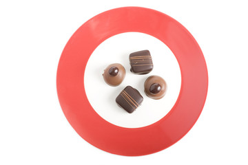 Four Gourmet Chocolates on Red and White Plate