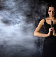 Attractively looking woman with a gun on a smoky background
