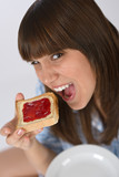 Happy teenager in pajamas eating healthy toast poster