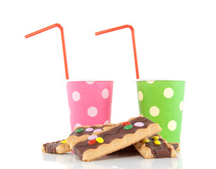 two colored drinking cups with straws and cookies isolated over