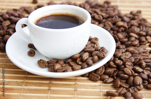 Fotobehang Koffiebonen cup of coffee on a background coffee-beans and bamboo serviette