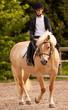 Ragazza bionda cavalca un pony