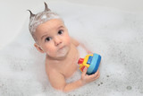Delighted baby having bath in shampoo foam poster