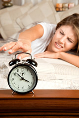 Young woman couch in the bed and turning off the alarm clock