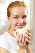 young smiling woman with a cup