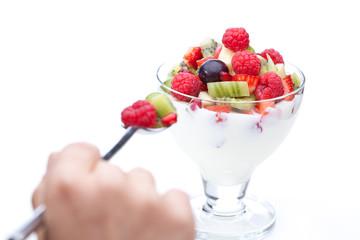 Hand mit Löffel und Früchten in Glas