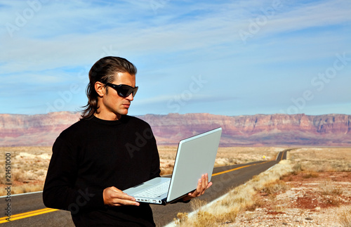Man on road with laptop