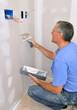 Man using drywall knife to finish seam between drywall sheets