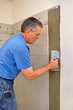 Man installing ceramic tiles in bathroom