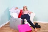 Woman slumped in an armchair after shopping trip