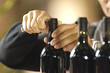 mani da uomo che stappano una bottiglia di vino rosso