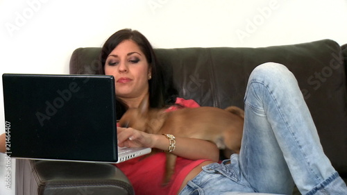 Pretty woman and her dog using a laptop sitting on sofa