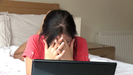 Disappointed woman looking at her laptop lying down on bed