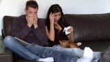 Dejected couple doing their accounts sitting on sofa at home