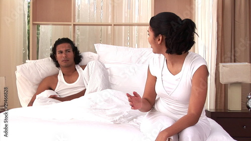 Frustrated couple having an argument sitting on bed
