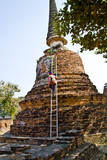 worker on ledder at a chedi, temple cleans the surface poster