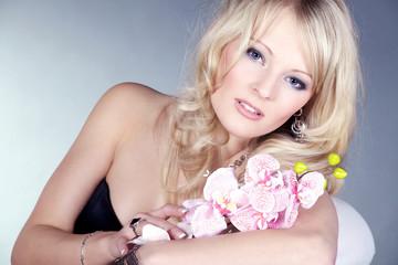 Blonde Frau mit Orchidee lieb blickend