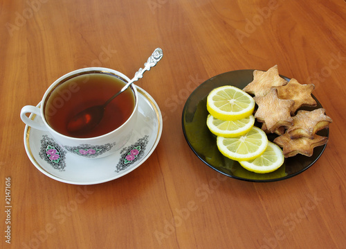 Tea, slices of lemon and cookies for breakfast