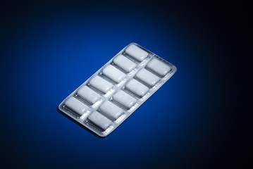 Package of nicotine gum on dark blue background