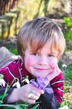 Kind hält einen Krokus in der Hand poster