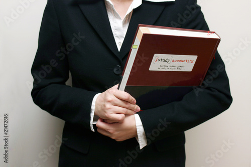 A woman hold a textbook.