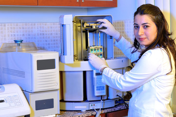 A pathology laboratory assistant working on specific equipment