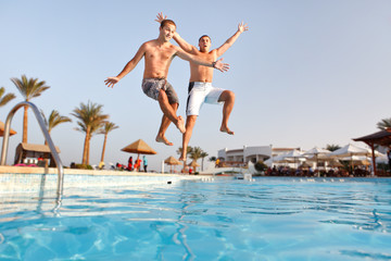 Two men jumping in swimming pool together